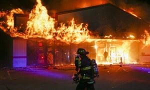A firefighter arrives to inspect a pizza business set ablaze in Ferguson
