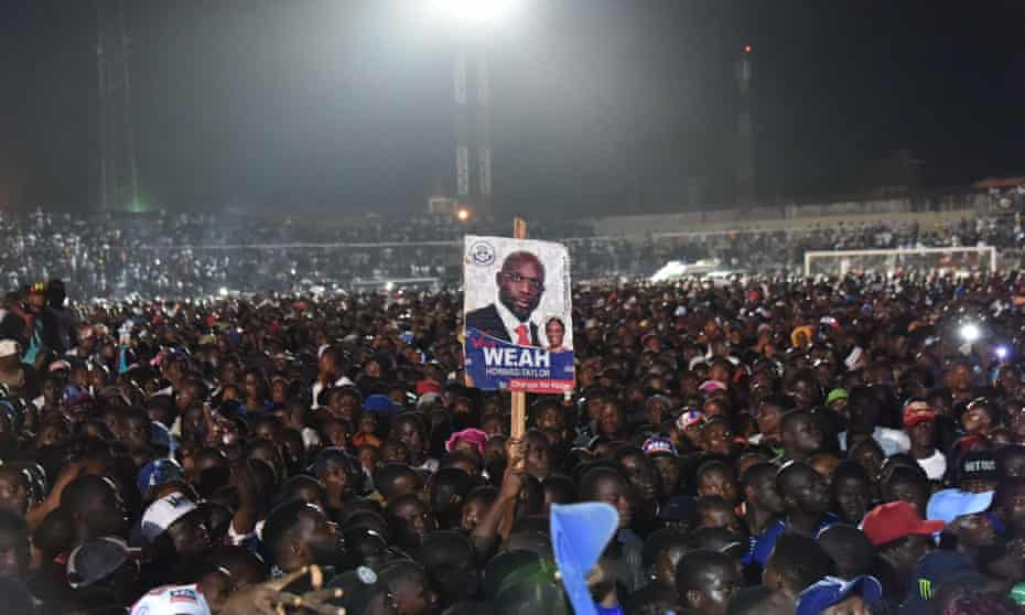 Supporters of former international Liberian football star turned politician George Weah hold up his poster as they attend a presidential campaign rally in Monrovia in October 2017.