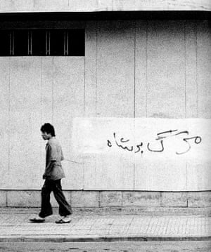 A man walks past a wall with 'Death to the Shah' scrawled over what appears to be similar graffiti previously covered up.