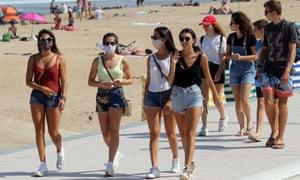 People wear face masks as they walk near the beach in Biarritz, southwestern France.