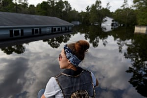 A member of a volunteer search and rescue team rides a boat to check homes for animals stranded in floodwater after Hurricane Florence hit in Bergaw, North Carolina, U.S., on Friday, Sept. 21, 2018.