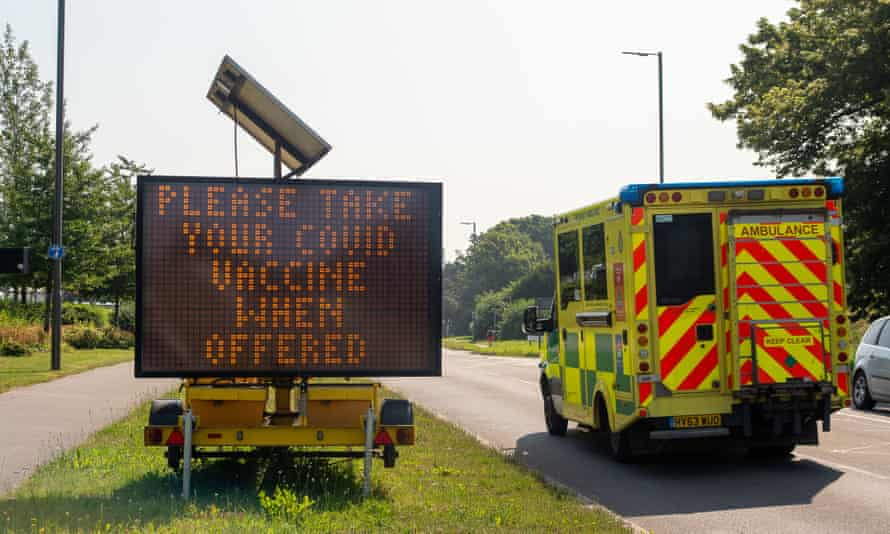 An emergency ambulance passes a large Please Take Your Covid Vaccine When Offered LED roadside sign on the A4.