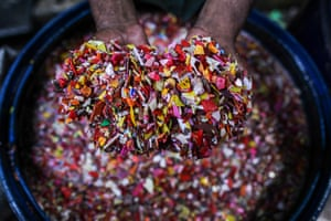 A worker washes shredded plastic waste for recycling