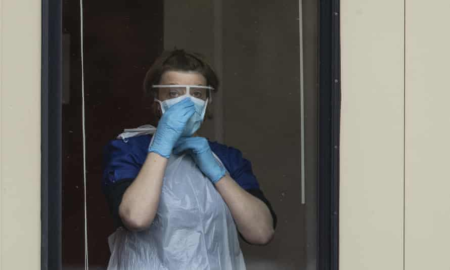 A nurse adjusts her face mask before taking swabs at a Covid-19 drive-through testing station for NHS staff in Chessington, UK.