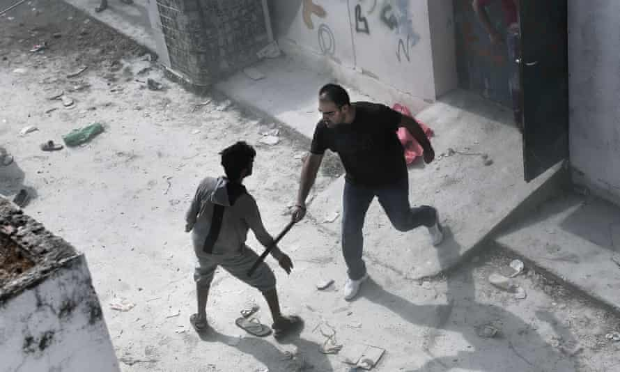A policeman hits a migrant with a truncheon.