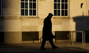 The silhouette of an older man walking along the street in Manchester