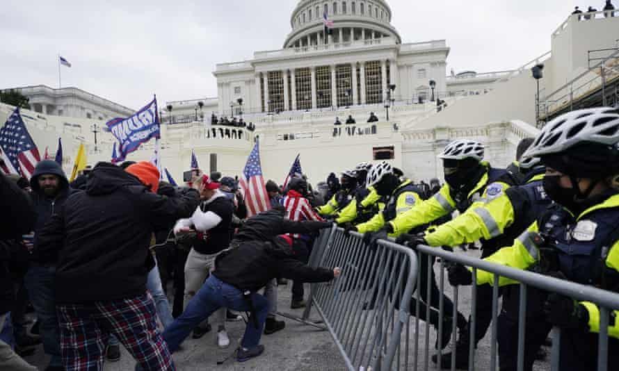 Capitol police struggle to prevent Trump supporters try from breaking through a barrier at the US Capitol on 6 January.