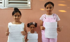 Ramy Almansoob's three daughters hold their recent visa denial letters.