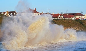 Waves crash against the sea wall at Seaham in County Durham