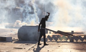 A protester wearing a gas mask takes part in anti-government protests in Sitra.
