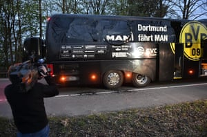 A cameraman films the Dortmund bus after it was damaged by explosions.