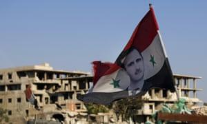 Now the clear winner: A Syrian flag bearing Bashar al-Assad's image in Douma, near Damascus.