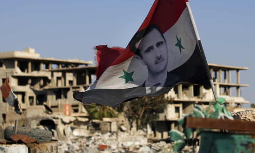 A Syrian national flag with a picture of Syrian President Bashar Assad flies at an Army check point, in the town of Douma in the eastern Ghouta region, near Damascus, Syria