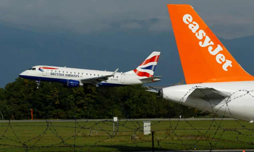 A British Airways aircraft lands next to a EasyJet plane ready for take off at Cointrin airport in Geneva