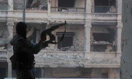 A Syrian rebel fires his rifle in Aleppo.