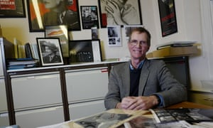 Tony Penrose at his desk at Farley Farm House surrounded by images of his mother