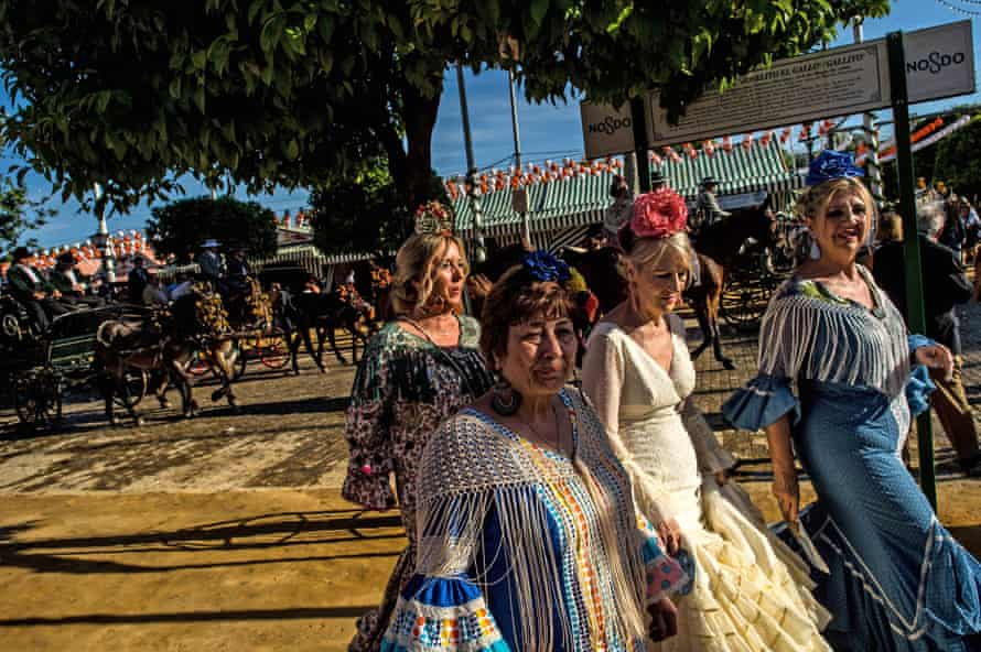 Women wearing traditional Sevillana dresses soak up the atmosphere at the Feria de Abril in Seville, Spain. The April fair, which dates to 1857, takes place annually a fortnight after Easter