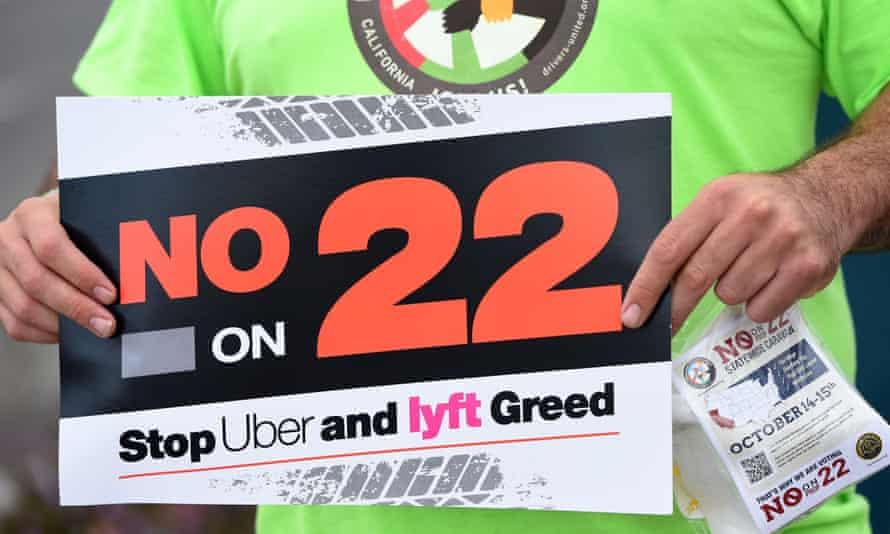 A rideshare driver holds up a sign supporting a no vote on Prop 22 in Oakland, California on October 9, 2020.