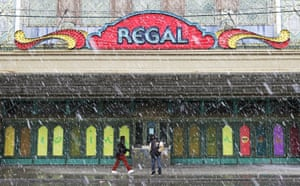 A woman walks past a man standing under the marquee of the Avalon Regal Theater as snow falls on East 79th Street in Chicago on 27 April 2019