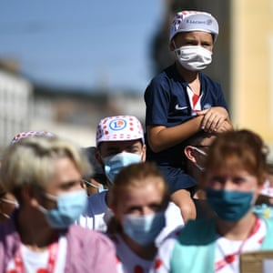 A child wearing face mask waits to see the riders before the start of the the 14th stage between Clermont-Ferrand and Lyon.
