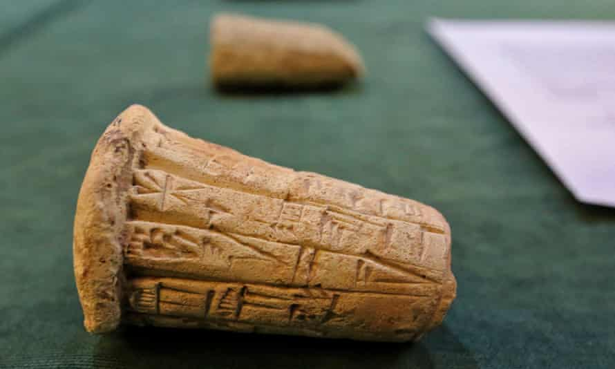 Mesopotamian clay cones bearing cuneiform inscriptions are displayed during the handover ceremony