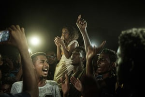 People chant slogans as a young man (not in picture) recites a poem illuminated by mobile phones