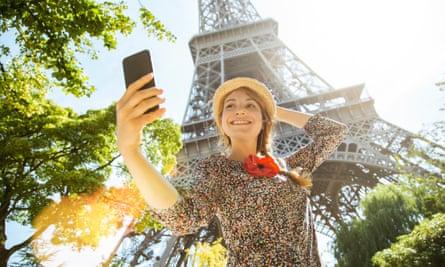 Woman taking selfie in front of Eiffel Tower