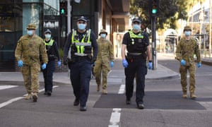 A group of police and soldiers patrol the Docklands area of Melbourne on August 2, 2020, after the announcement of new restrictions to curb the spread of the COVID-19 coronavirus. - Australia on August 2 introduced swe