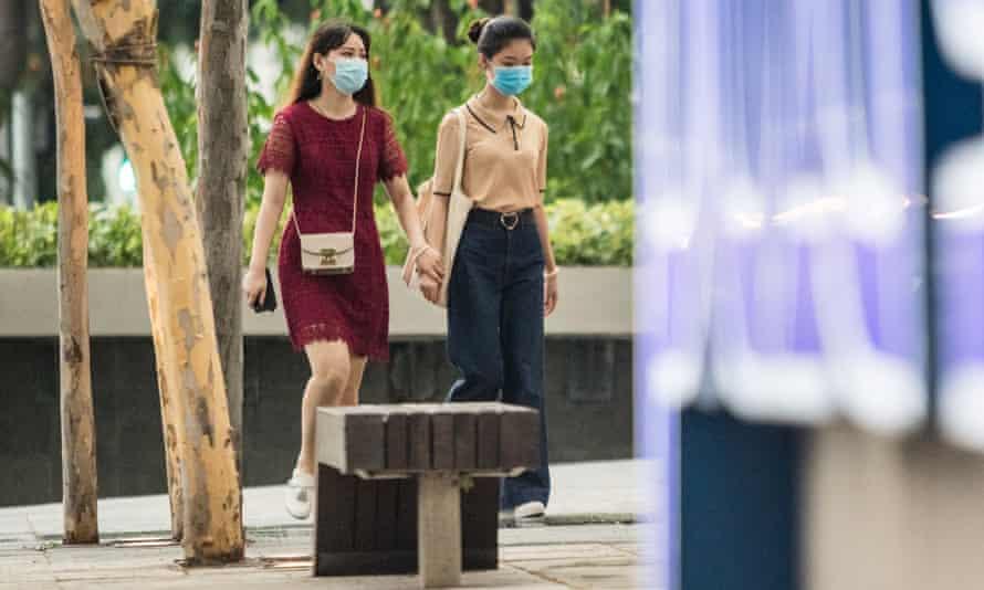 two women in masks walking in singapore