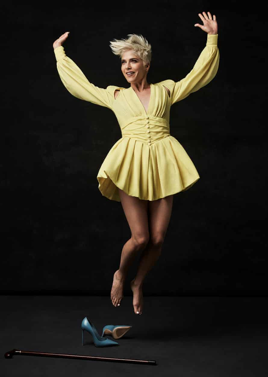 Selma jumping with her arms up, wearing a yellow dress with a ra-ra skirt