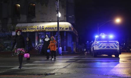 Trick-or-treaters walk past a crime scene where a seven-year-old girl was shot in Chicago on Thursday.