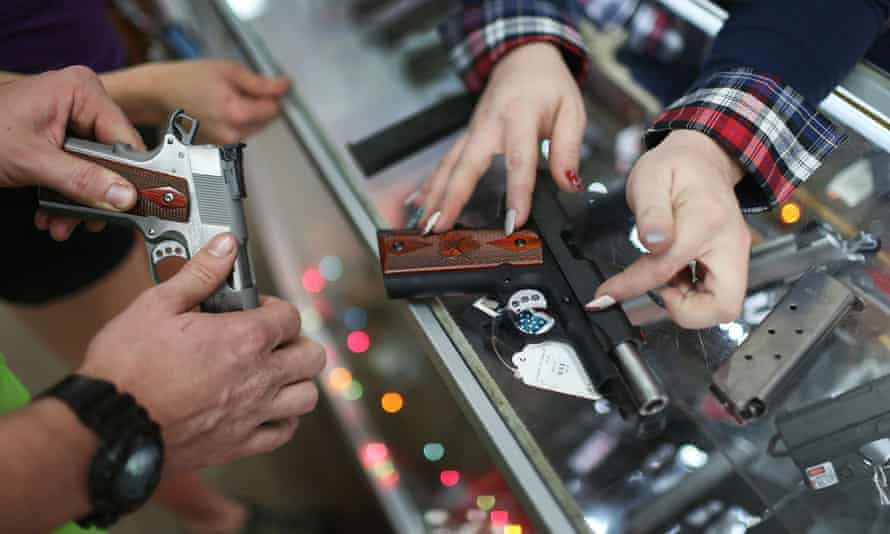 A customer compares handguns before buying one as a Christmas present at the National Armory gun store in Florida.