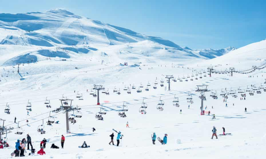 View of a snow track in Sierra Nevada (Spain) with chairlifts. There is some people skiing in the picture.