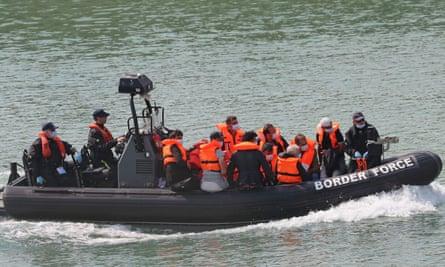 People in orange life vests aboard a Border Force boat