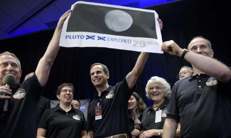 Dr. Alan Stern (left), principal investigator for the New Horizons mission other team members celebrate the success of the flyby.
