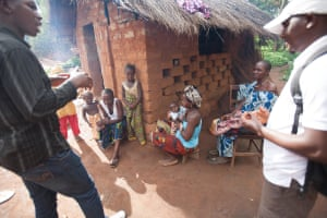 Representatives of the WHO vaccine trial team speak to families on a door-to-door basis about the Ebola vaccine trial