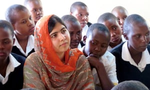 Malala Yousafzai looking thoughtful with a group of boys in school uniform