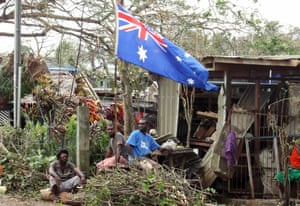 Local residents sit outside their damaged homes surrounded by debris on a street after cyclone Pam hit Port Vila.