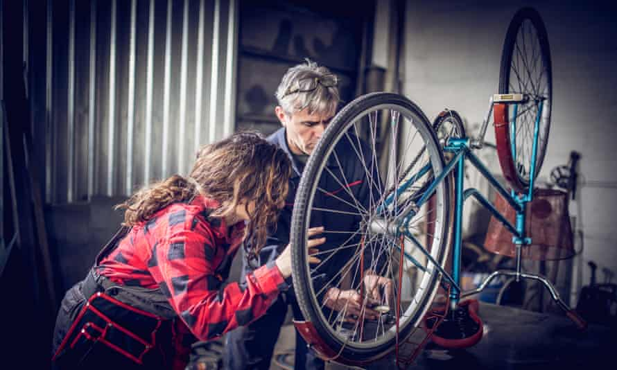 Senior man and young woman working on a bike in a workshop together.
