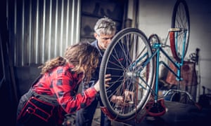 A man and a girl work on a bike in a workshop