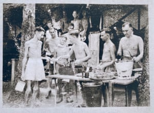 Bill Norways (centre) serves food to fellow PoWs.