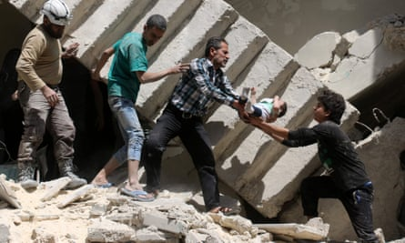 Volunteers and rescuers rescue a baby from the rubble of a destroyed building after a reported airstrike on the rebel-held neighbourhood of al-Kalasa in Aleppo