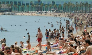 People cool off on Barceloneta's beach during a hot spring day.