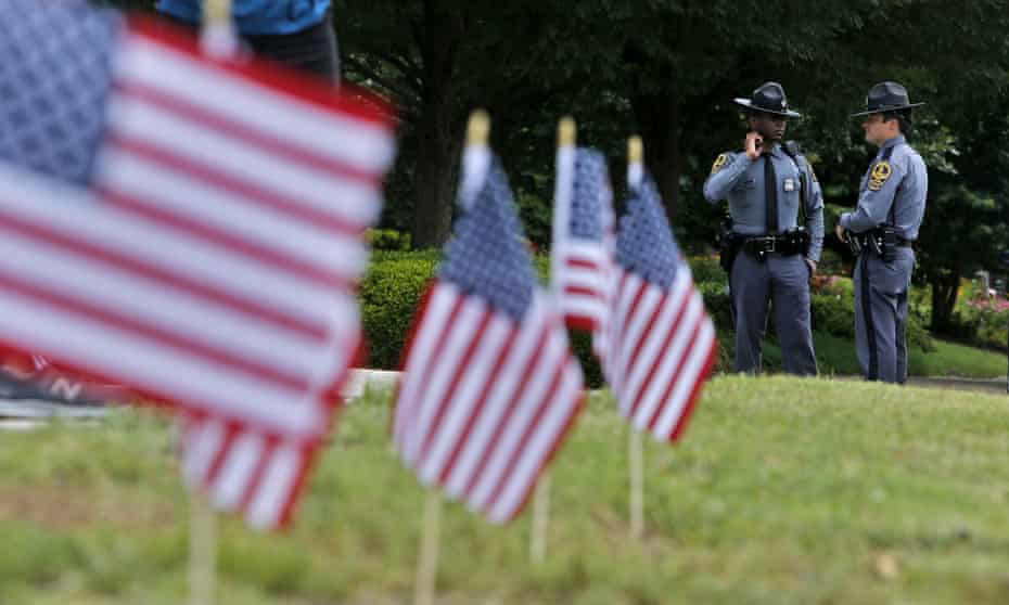 Virginia State Troopers stand near a memorial at the Virginia Beach Municipal Center.