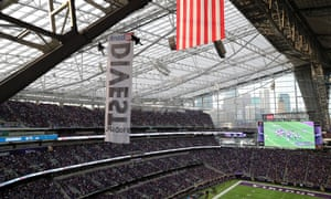 Two protesters hang suspended from ropes above the Minnesota Vikings and Chicago Bears football game.