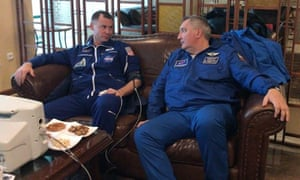 American astronaut Nick Hague (L) speaks to Roscosmos's director Dmitry Rogozin after the emergency landing.