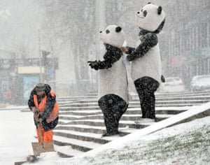 A city worker in Kiev, Ukraine, shovels snow from steps, watched by people dressed as pandas