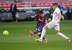 Lionel Messi of Barcelona shoots past Federico Valverde of Real Madrid.