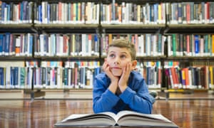 Boy with book on library floor