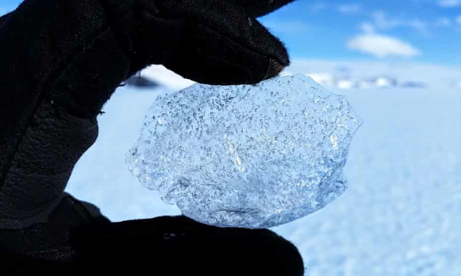 a gloved hand holding a ball of ice